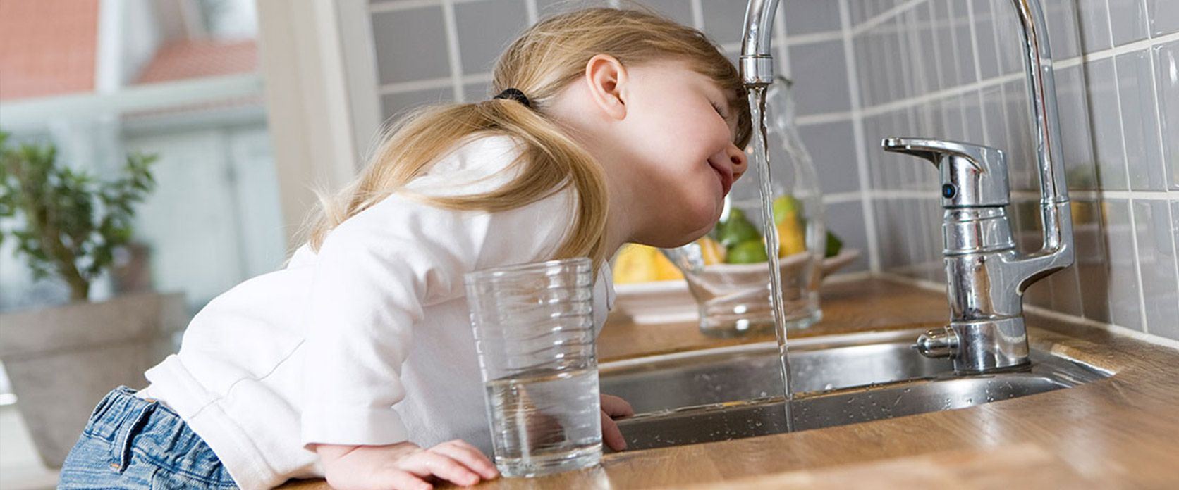 kid drinking from faucet